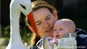 Eine Mutter hält ein Baby im Arm und sitzt mit ihm vor einem Spielzeugstorch