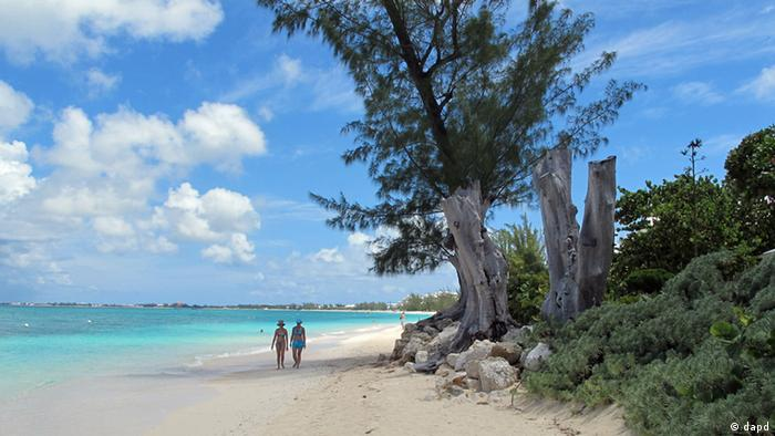 In this Aug. 3, 2012 photo, tourists walk along the beach of Seven Mile Beach in Grand Cayman Island. The Cayman Islands have lost some of their allure by abruptly proposing what amounts to an income tax on expatriate workers who have helped build the territory into one of the most famous or, for some people, notorious offshore banking centers that have tax advantages for foreign investment operations. (Foto:David McFadden/AP/dapd)