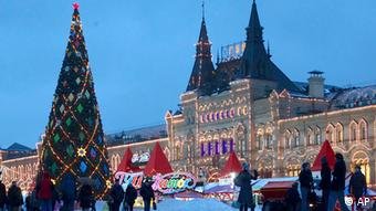 In this Dec. 4, 2012 file photo, people walk past a Christmas tree in Red Square, with the GUM State Department Store at right, in Moscow. (Foto:Alexander Zemlianichenko, File/AP/dapd)
