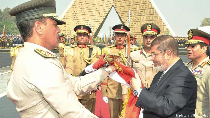 Egyptian President Mohamed Morsi (second right) kissing the national flag next to Minister of Defence Abdel Fattah al-Sissi (Photo: dpa)