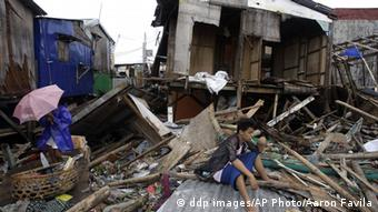 A man sits outside a damaged house after powerful Typhoon Nesat wiped out most of the homes near the bay along a coastal village in Navotas, north of Manila, Philippines on Wednesday Sept. 28, 2011. Emergency services and residents in the Philippine capital cleaned up and restored electricity Wednesday after the powerful typhoon unleashed floodwaters and fierce wind that killed at least 20 people and sent huge waves crashing over seawalls.