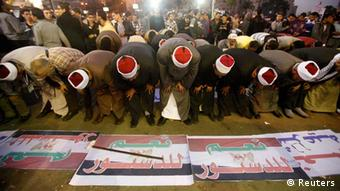 Supporters of Egypt's President Mohammed Morsi perform prayers during a rally held to show support to him in Cairo December 11, 2012. The banners read, Yes to the constitutions! and Yes to the legitimacy! REUTERS/Khaled Abdullah