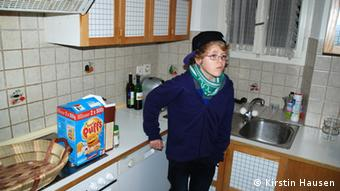 An early teens child wearing a black baseball cap stands in a small kitchen where little more than a box of cereal can be seen. (Photo: opyright Kirstin Hausen=