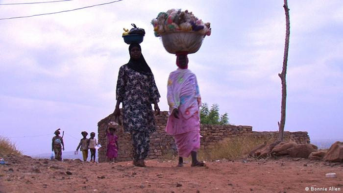 Displaced women from northern Mali walking in Bamako carrying loads on their heads Source: Bonnie Allen