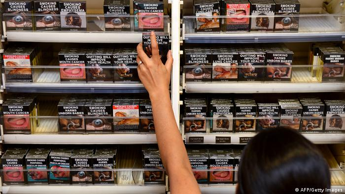 An employee in a bookshop adjusts packaged cigarettes which have to be sold in identical olive-brown packets bearing the same typeface and largely covered with graphic health warnings, with the same style of writing so the only identifier of a brand will be the name on the packet, in Sydney on December 1, 2012. A new world-first law forcing tobacco companies to sell cigarettes in identical packets came into effect Saturday in Australia in an effort to strip any glamour from smoking and prevent young people from taking up the habit. AFP PHOTO/William WEST (Photo credit should read WILLIAM WEST/AFP/Getty Images) ধূমপান রোধে এলো প্রযুক্তির নতুন কৌশল