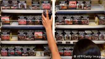 An employee in a bookshop adjusts packaged cigarettes which have to be sold in identical olive-brown packets
