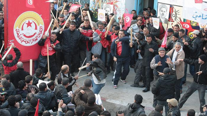 Members of the leftist UGTT union, background, react during clashes with League members Foto:Amine Landoulsi/AP/dapd