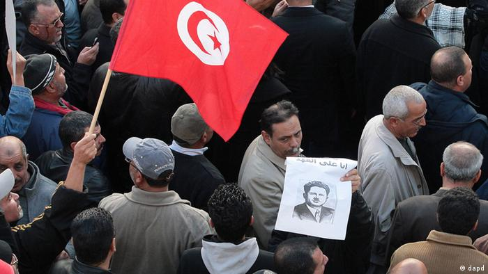 Members of the leftist UGTT union march, one holding a portrait of Farhat Hached, during a rally to commemorate his 1955 assassination of a historic member when they were attacked by the League for Protection of the Revolution, Tuesday, Dec. 4, 2012 in Tunis. League members are considered to be close to the Ennahda Party, which dominates Tunisia's post-revolution coalition government (Foto:Amine Landoulsi/AP/dapd)
