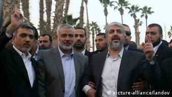 Image #: 20449485 Hamas leader in exile Khaled Meshaal waves goodbye while standing next to Palestinian Prime Minister in the Gaza Strip Ismail Haniya and Hamas leader Izzat al-Rishq, upon his departure from the Gaza Strip on December 10, 2012 in Rafah, on the border with Egypt. (Eyad Al Baba APA /Landov)