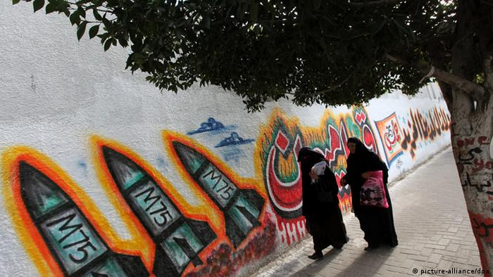 Palestinian muslim students walk past murals of M75 rockets painted by Ezzedine al-Qassam brigades, the armed wing of the Hamas movement (EPA/MOHAMMED SABER)