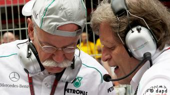Norbert Haug and Dieter Zetsche compare notes, studying an unseen object/document together. (Photo via dapd)