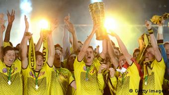 Dortmund's midfielder Sebastian Kehl (C) holds up the trophy and celebrates with teammates after winning the German cup DFB Pokal final football match Borussia Dortmund vs Bayern Munich at the Olympiastadion in Berlin on May 12, 2012. Dortmund defeated Munich 5-2. (Photo: ODD ANDERSEN/AFP/GettyImages)