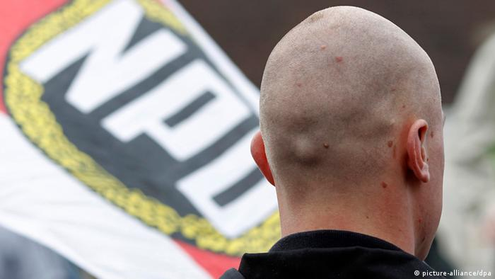 An man with a shaved head is shown from behind in front of an NPD flag. (Photo: picture-alliance/ dpa)
