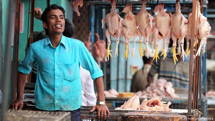 A man standing in front of his stall, from which a row of plucked chickens are hanging, at a market in Bangalore. (Photo: Jan Woitas/dpa)