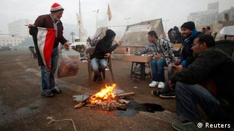 Protesters opposing Egyptian President Mohamed Mursi sit around a fire to warm themselves up at Tahrir Square in Cairo December 14, 2012. Supporters and opponents of Mursi stage final rallies on Friday before a divisive referendum on a new constitution championed by the Islamist leader as a way out of the worst crisis since the fall of Hosni Mubarak. REUTERS/Khaled Abdullah (EGYPT - Tags: POLITICS CIVIL UNREST)