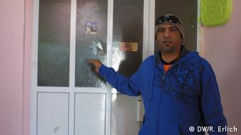 Abdullah al Mizo points to a broken window in his apartment (photo: Reese Erlich)
