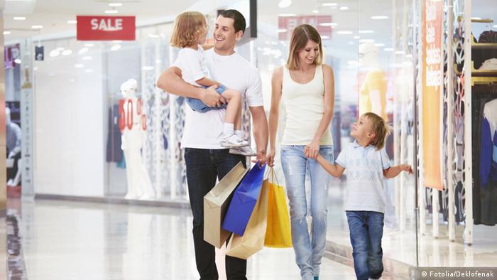Родители и двое детей идут с покупками - фото, символизирующее немецкий средний класс