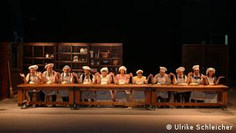 Actors sitting at a long table on stage at the Nalaga'at Theater