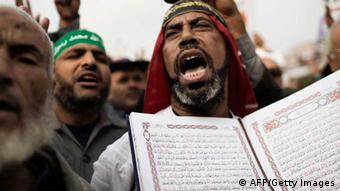A supporter of Egypt's President Mohamed Morsi and the Muslim Brotherhood holds a Koran, Islam's holy book, as he shouts slogans during a demonstration in the Nasser City district of Cairo on December 14, 2012. Weeks of protests and violent clashes between rival camps that left eight people dead last week have failed to dissuade Morsi from holding the referendum, which will be staggered over a week. AFP PHOTO/MARCO LONGARI (Photo credit should read MARCO LONGARI/AFP/Getty Images)