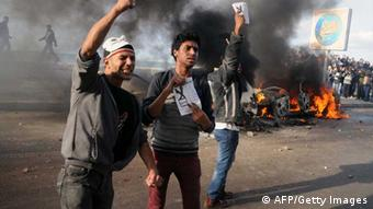 Egyptian protesters shout slogans in front of burning cars set on fire during a demonstration calling for a 'No' vote in a referendum on a new constitution in the coastal city of Alexandria on December 14, 2012. Stone-throwing clashes broke out between Islamists and opposition supporters in Alexandria on the eve of the highly charged referendum, witnesses said. There was no immediate word on any casualties but witnesses told AFP street violence was continuing in Egypt's second-biggest city despite police efforts to restore order. AFP PHOTO/STR (Photo credit should read STR/AFP/Getty Images)