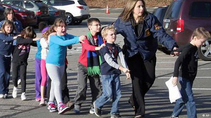 In this photo provided by the Newtown Bee, Connecticut State Police lead children from the Sandy Hook Elementary School in Newtown, Conn., following a reported shooting there Friday, Dec. 14, 2012. (Foto:Newtown Bee, Shannon Hicks/AP/dapd) MANDATORY CREDIT