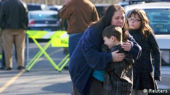 A young boy is comforted outside Sandy Hook Elementary School Michelle McLoughlin