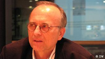 Dušan Reljić, a middle-aged man wearing glasses, looks off camera in an indoor setting. Photo: Deutschen Welle.