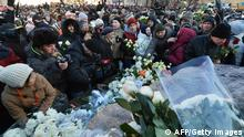People lay flowers on a monument dedicated to victims of political repression during an opposition protest marking one year since the start of protests against Vladimir Putin, in Moscow, on December 15, 2012. Russian police arrested top opposition leaders at the anti-Vladimir Putin rally in central Moscow attended by hundreds of people in defiance of a ban by the authorities. Police arrested Ilya Yashin, a leading figure in the Solidarity movement as well as TV presenter Ksenia Sobchak, Yashin said on Twitter. AFP PHOTO/ NATALIA KOLESNIKOVA (Photo credit should read NATALIA KOLESNIKOVA/AFP/Getty Images)