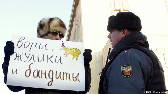 Участник протестной акции в декабре 2012 года в Москве с плакатом Воры, жулики и бандиты, рядом с ним - полицейский