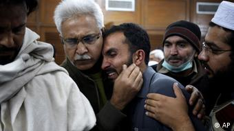 A Pakistani man comforts another mourning over the death of his relative, a victim of a rocket attack by militants, at a local hospital in Peshawar, Pakistan on Saturday, Dec. 15, 2012 (Photo: Mohammad Sajjad/AP/dapd)