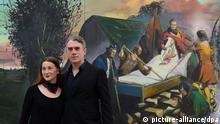 Das Leipziger Künstlerpaar Neo Rauch und Rosa Loy steht am 14.12.2012 in den Kunstsammlungen Chemnitz (Sachsen) vor dem Gemälde «Der böse Kranke» (2012)von Neo Rauch. Es ist die erste gemeinsame Doppelausstellung des Paares in Deutschland. Zu sehen sind 23 Arbeiten in getrennten Räumen unter den Titeln «Abwägung» und «Gravitation». Foto: Hendrik Schmidt/dpa +++(c) dpa - Bildfunk+++
