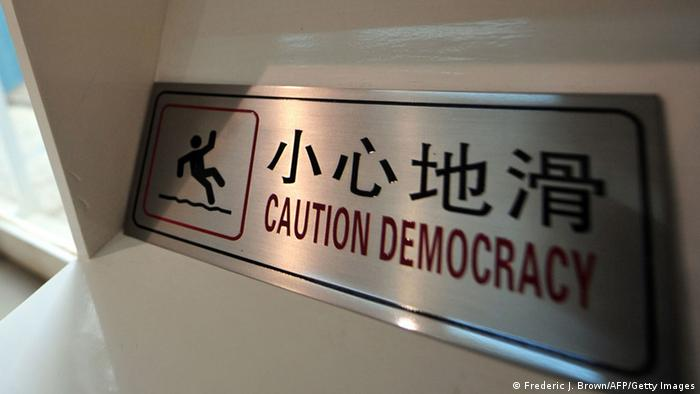 A sign used at an arts exhibition in Beijing in 2009 which reads 'Caution Democracy' in a poor translation of the Chinese characters which read 'caution slippery.' Photo: FREDERIC J. BROWN/AFP/Getty Images)