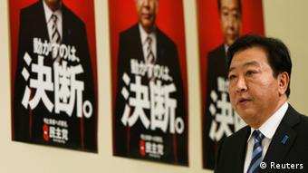 Japan's former prime minister Yoshihiko Noda, leader of the Democratic Party of Japan (DPJ), arrives at a news conference with posters of himself reading Decision in the background, at his party's election headquarters in Tokyo December 16, 2012 (Photo: REUTERS/Issei Kato)