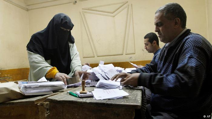 An older Egyptian woman wearing a black headscarf passes her vote to two men sitting at a table in a small room. (Photo:Amr Nabil/AP/dapd)