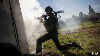 In this Saturday, Dec. 15, 2012 photo, a Free Syrian Army fighter fires a weapon during heavy clashes with government forces at a military academy besieged by the rebels north of Aleppo, Photo:Narciso Contreras/AP/dapd