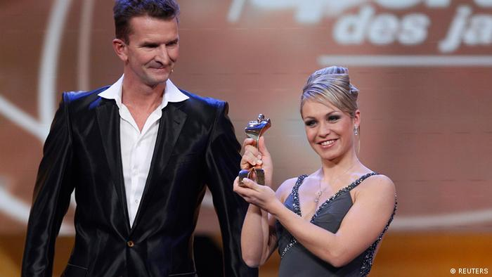 German biathlete Magdalena Neuner (R) reacts with the Sportswoman of the year trophy next to former German swimmer Michael Gross during a gala in Baden Baden December 16, 2012. REUTERS/Lisi Niesner (GERMANY - Tags: SPORT ENTERTAINMENT BIATHLON)