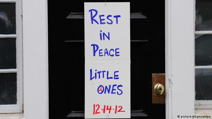 A sign reading Rest in Peace Little Ones' hangs on the front door of a house in Newtown, Connecticut
