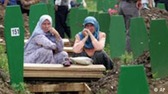 Bosnian Muslim women sit at Potocari cemetery, outside Srebrenica
