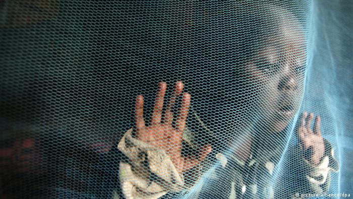 A girl leans against a mosquito net (Photo: Stephen Morrison)