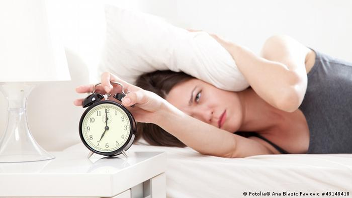 Woman turning off alarm clock and holding a pilllow over her head (Copyright: Fotolia/Ana Blazic Pavlovic)