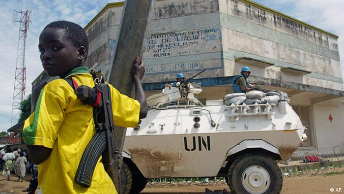 FILE In this May 30, 2003 file photo, a child fighter of the rebel Union of Congolese Patriots, then in control the Congolese town of Bunia, stands near a United Nations armored personnel carrier near the UN compound in Bunia, Congo. Judges at a war crimes tribunal Wednesday, March 14, 2012, convicted Congolese warlord Thomas Lubanga of snatching children from the street and turning them into killers, in the International Criminal Court's landmark first judgment 10 years after it was established. Prosecutors said Lubanga led the Union of Congolese Patriots political group and commanded its armed wing, the Patriotic Forces for the Liberation of Congo, which recruited children 'sometimes by force, other times voluntarily' into its ranks to fight in a brutal ethnic conflict in the Ituri region of eastern Congo.(Foto:Karel Prinsloo/AP/dapd).