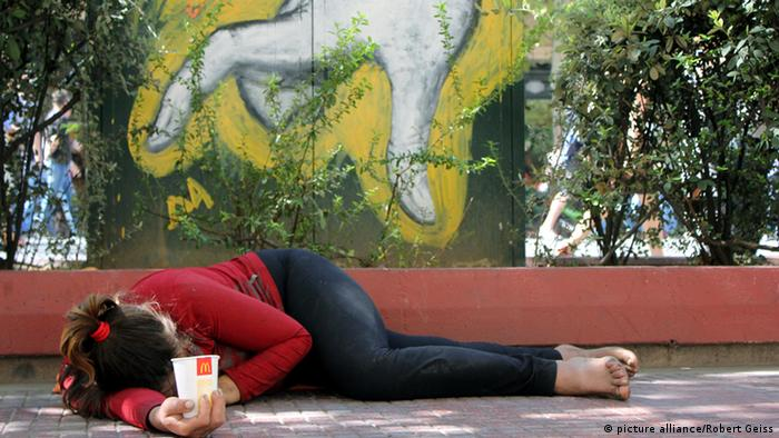 A homeless woman lays on an Athens sidewalk