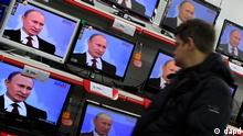 A person watches a live television broadcast showing Russian Prime Minister Vladimir Putin attending a national call-in TV show as it is shown on several screens at a store in Moscow, Russia, Thursday, Dec. 15, 2011. Putin said Thursday the results of Russia's parliamentary election reflected the people's will, and that the opposition had alleged vote fraud purely to strengthen its position. The results of this election undoubtedly reflect the real balance of power in the country, he said, speaking in a national call-in TV show. It's very good that United Russia has preserved its leading position. He added that a drop in support for his party was a natural result of the global financial crisis of 2008 that has taken its toll on the country. (Foto:Ivan Sekretarev/AP/dapd)