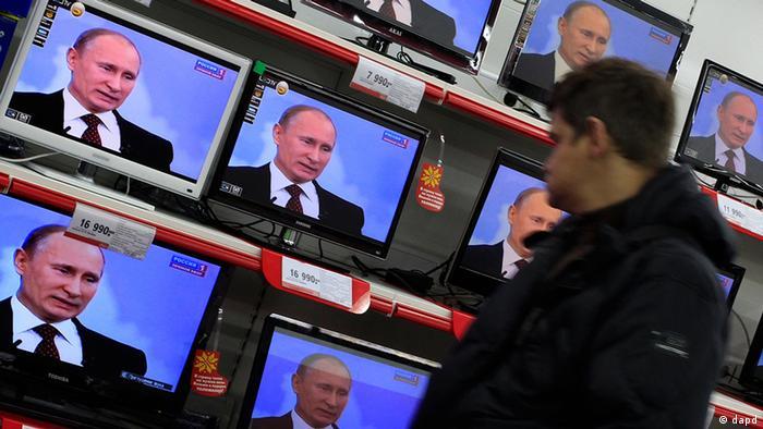 Посетитель в магазине, где на экранах всех телевизоров показывают выступление Путина