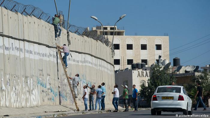 Palestinians use a ladder to cross over a wall Picture by Johanna Geron