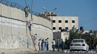20120810 - RAMALLAH, WEST BANK : Palestinians mens use a ladder to cross over the separate wall over the separated wall at the palestinian town of A-RAm, north of Jerusalem. Friday 10 august 2012 in Ramallah West Bank. Picture by Johanna Geron