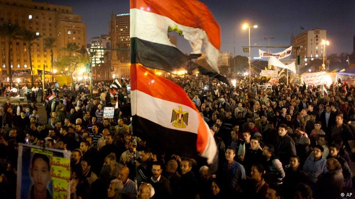 Egyptians opposing president Mohammed Morsi fly their national flags as one holds a poster with a picture of a slain protester with Arabic that reads Martyr Mostafa Helmi, down with the rule of the Morshid, during a rally in Tahrir Square, Cairo, Egypt, Tuesday, Dec. 18, 2012. (Foto:Nasser Nasser/AP/dapd)