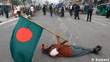 An activist of the Communist Party of Bangladesh (CPB) holds a Bangladesh flag as he lies down on a street during a strike in Dhaka December 18, 2012. The CPB and the Bangladesh Samajtantrik Dal (BSD) called for a countrywide shutdown on Tuesday, demanding a ban on the Jamaat-e-Islami, a radical Islamist party, and for a quicker trial of war criminals, local media reported. REUTERS/Andrew Biraj (BANGLADESH - Tags: CIVIL UNREST POLITICS TPX IMAGES OF THE DAY)