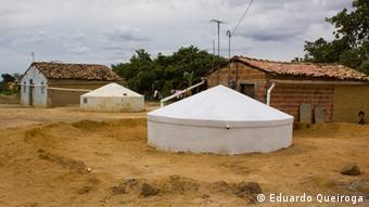 Zwei Lehmziegelhäuser mit etwa weißen Betonzisternen davor, die rund zwei Meter aus dem Boden ragen und einen Durchmesser von rund acht Metern haben. Die Umgebung besteht aus gelblichen Gräsern und Büschen. (Foto: Eduardo Queiroga)