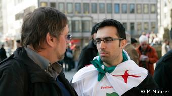Karl Korn talks outside to man wearing a Syrian flag Photo: Michael Maurer